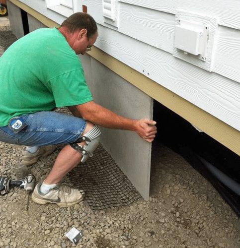 man installing cement-concrete skirting